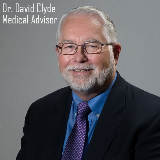 Dr. David Clyde Dressed in Suit with a Blue Shirt and Purple Tie with Gray Dots