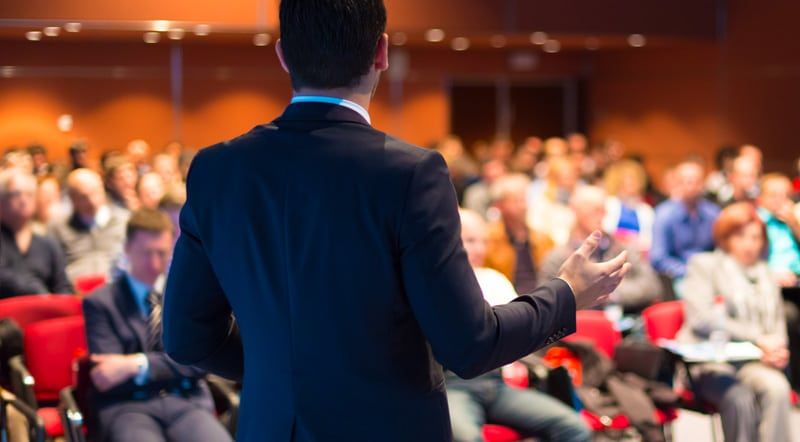 Business executive speaking in front of people in a room