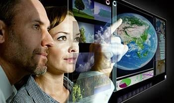 Woman and man looking at transparent screen with a globe on it