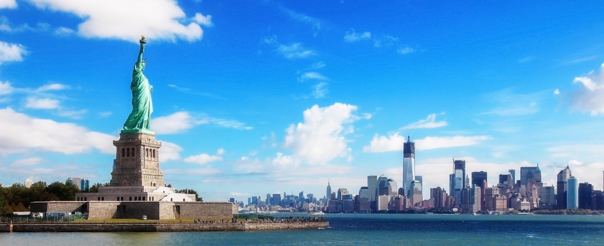 Statue of Liberty and NYC skyline on sunny day